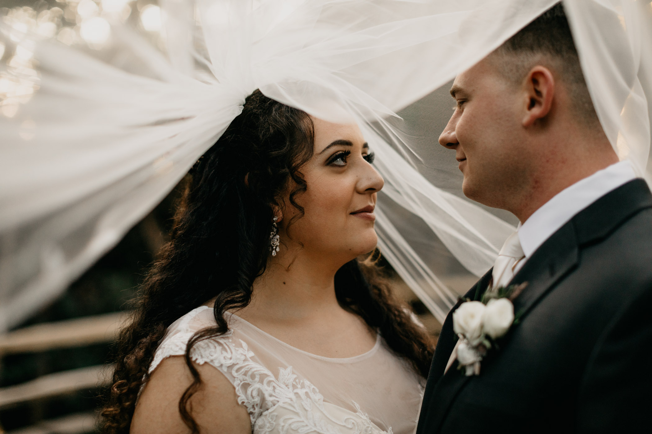 Bride and groom under veil in California on wedding day