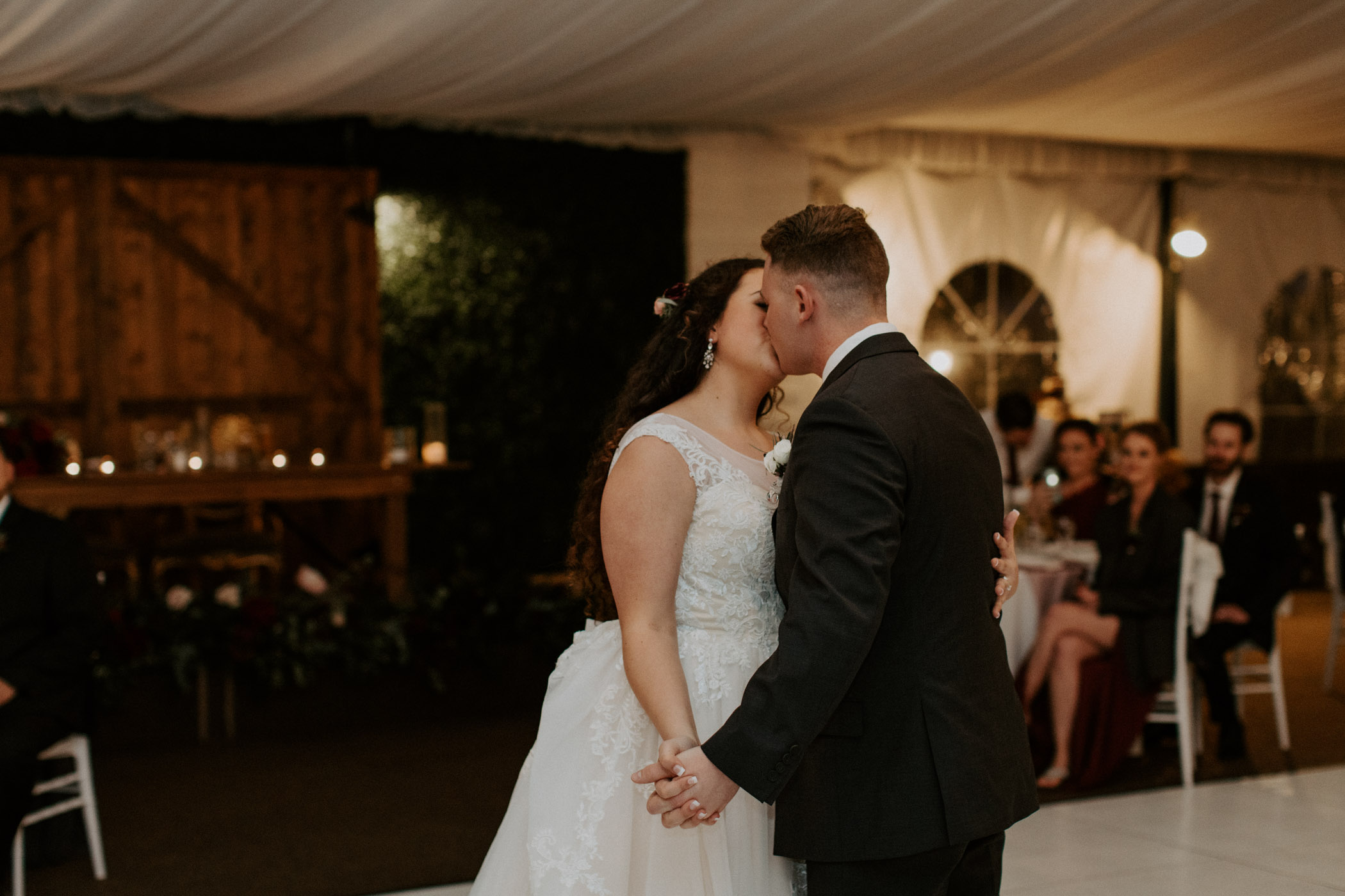Bride and groom kissing romantically during their first dance