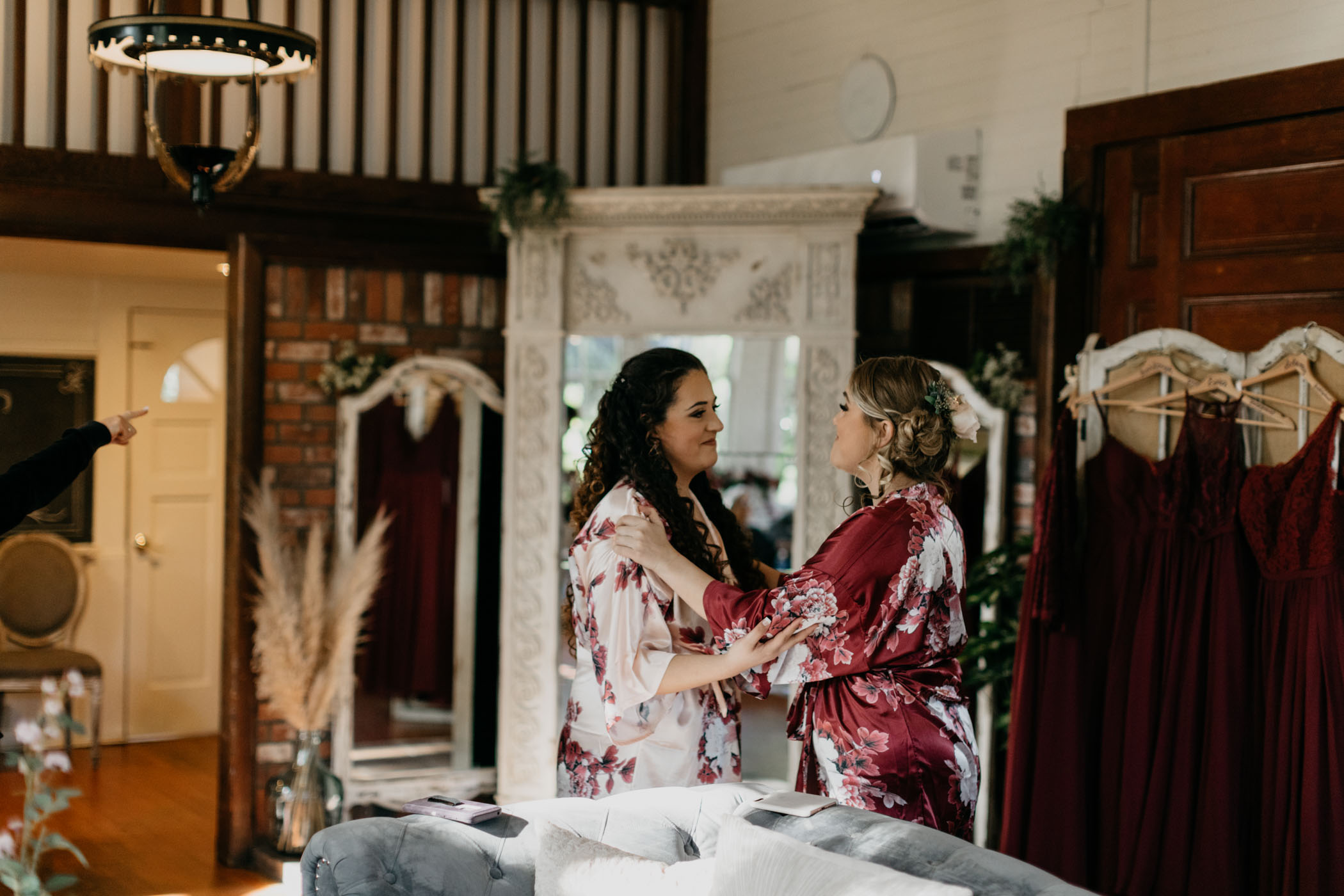 Bride getting ready in bridal room with bridesmaid