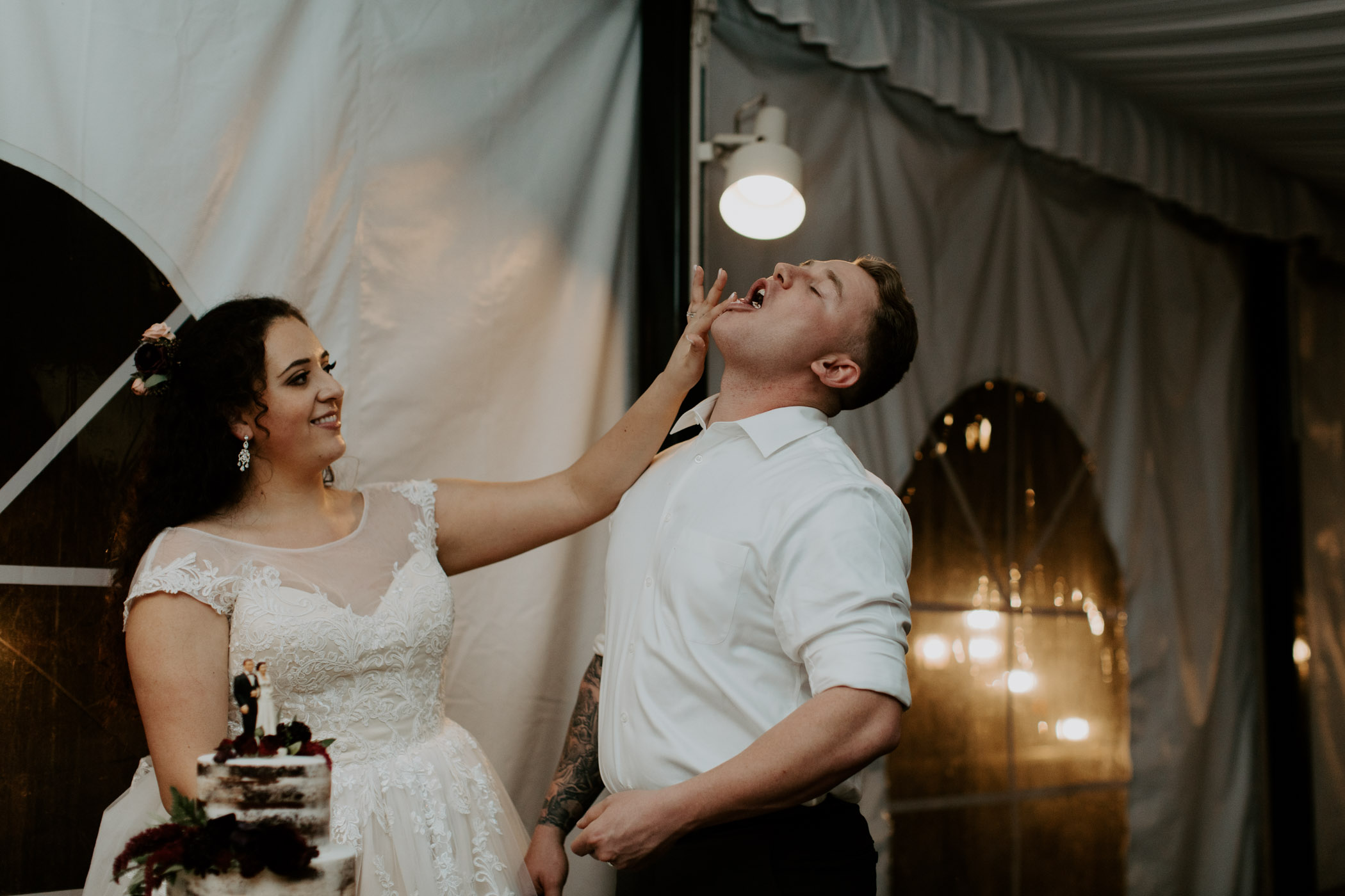 Bride playfully shoving cake in grooms mouth on their wedding day