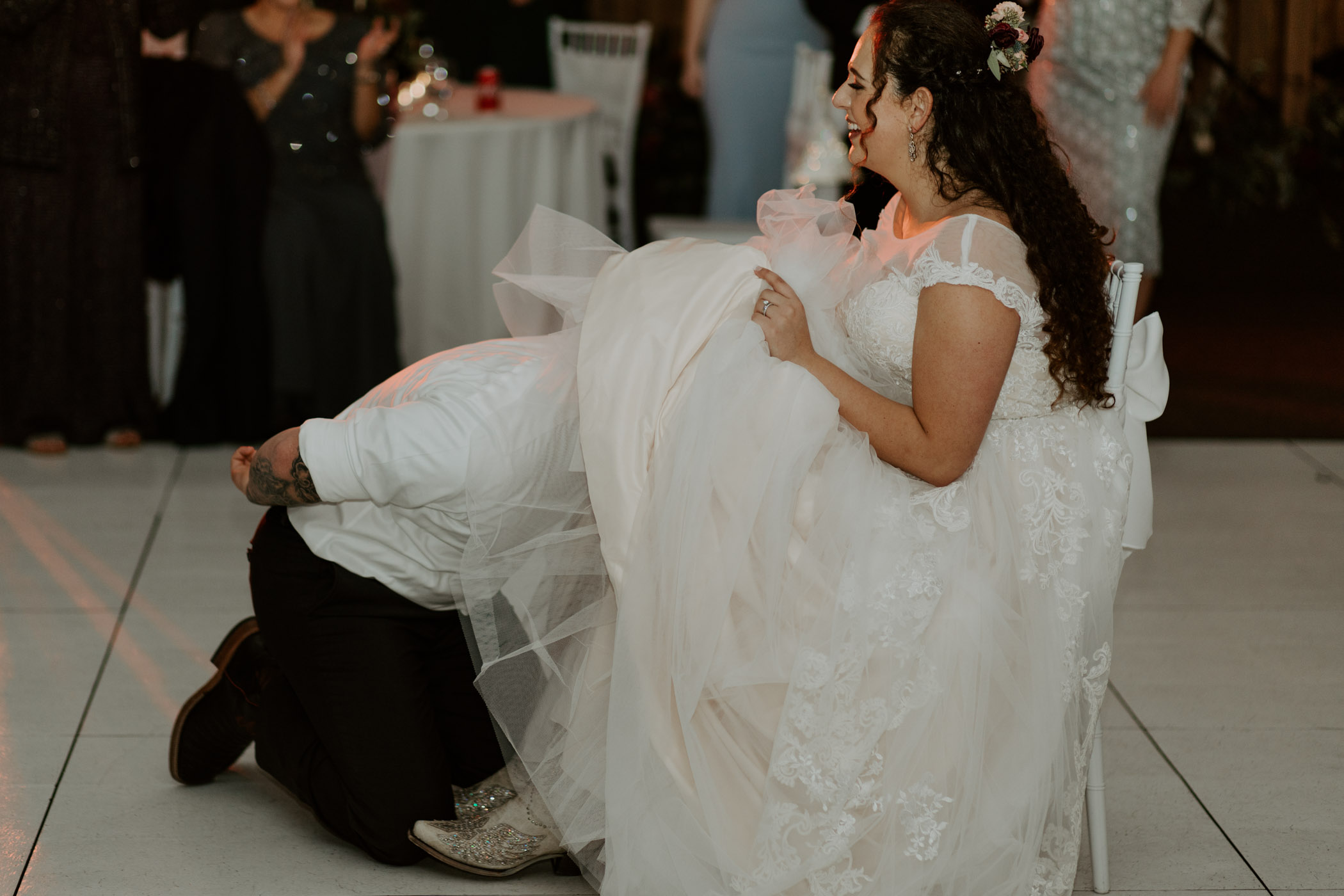 Groom taking off brides garter without his hands