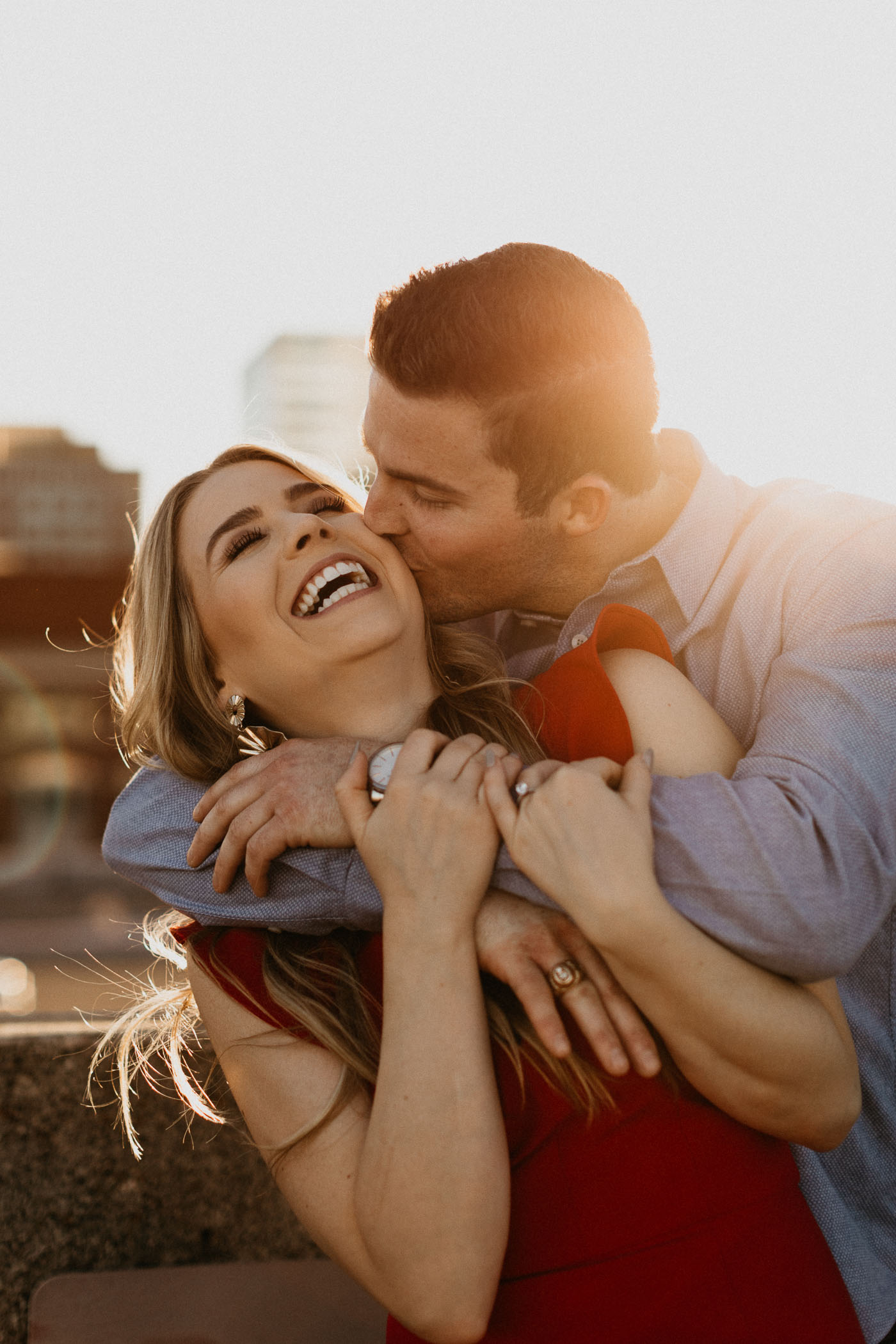 couple kissing on a rooftop in downtown Fort Worth during engagement session