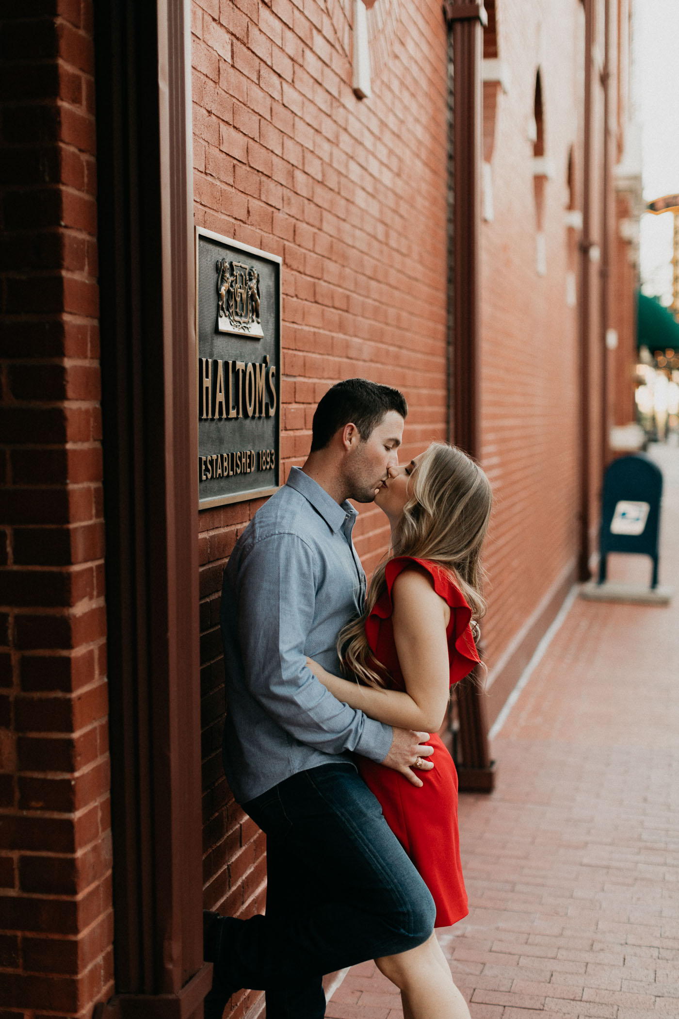 Boy leaning against brick wall during Fort Worth downtown engagement session