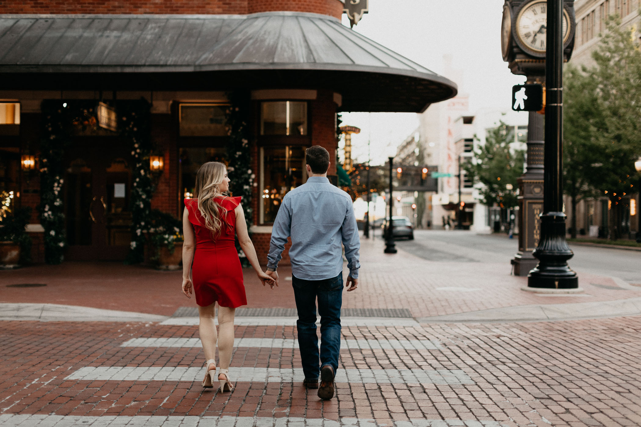 couple holding hands and walking across Main Street in downtown Fort Worth