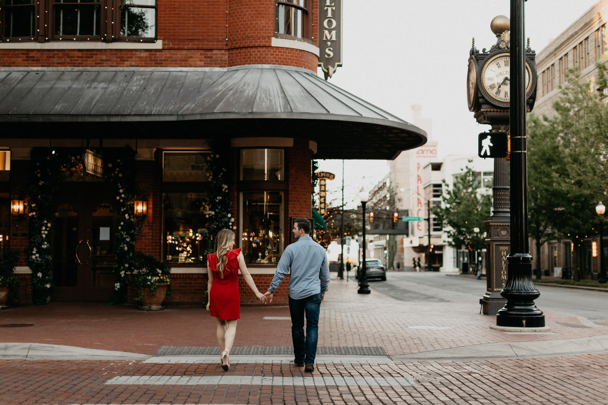 couple holding hands and walking across Main Street in Downtown Fort Worth Sundance square