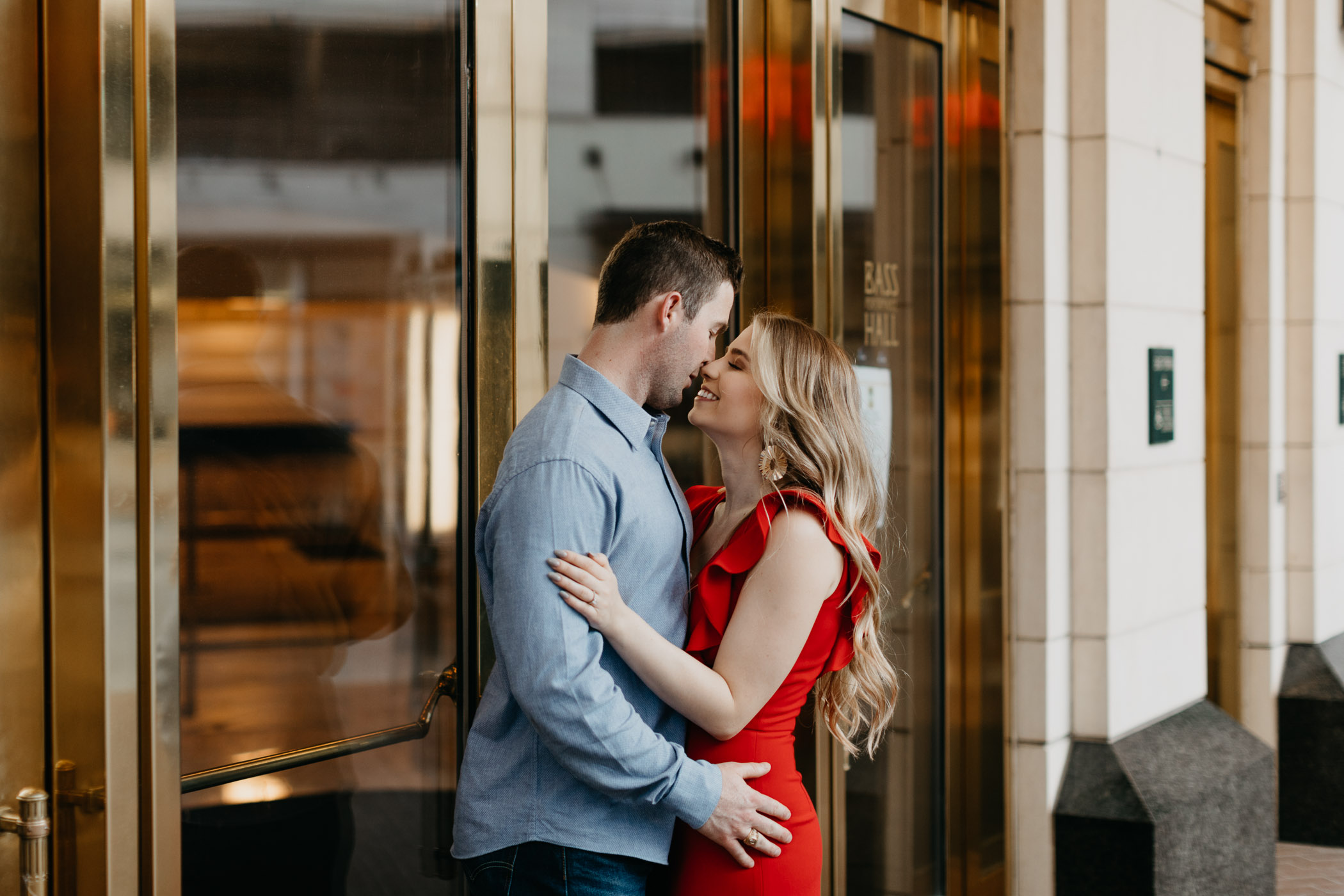 adorable couple looking at each other in front of Bass Hall in Downtown Fort Worth