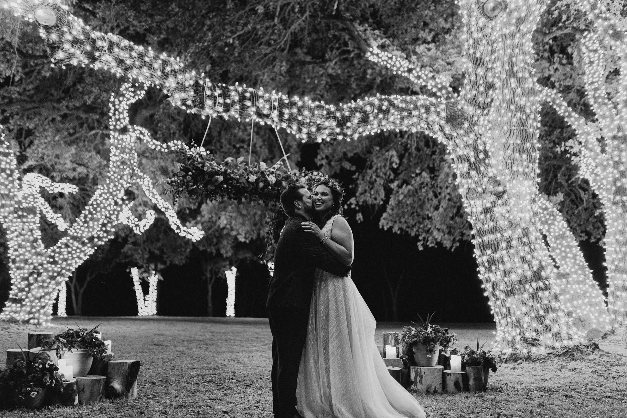 Image lit by string lights of bride and groom being romantic