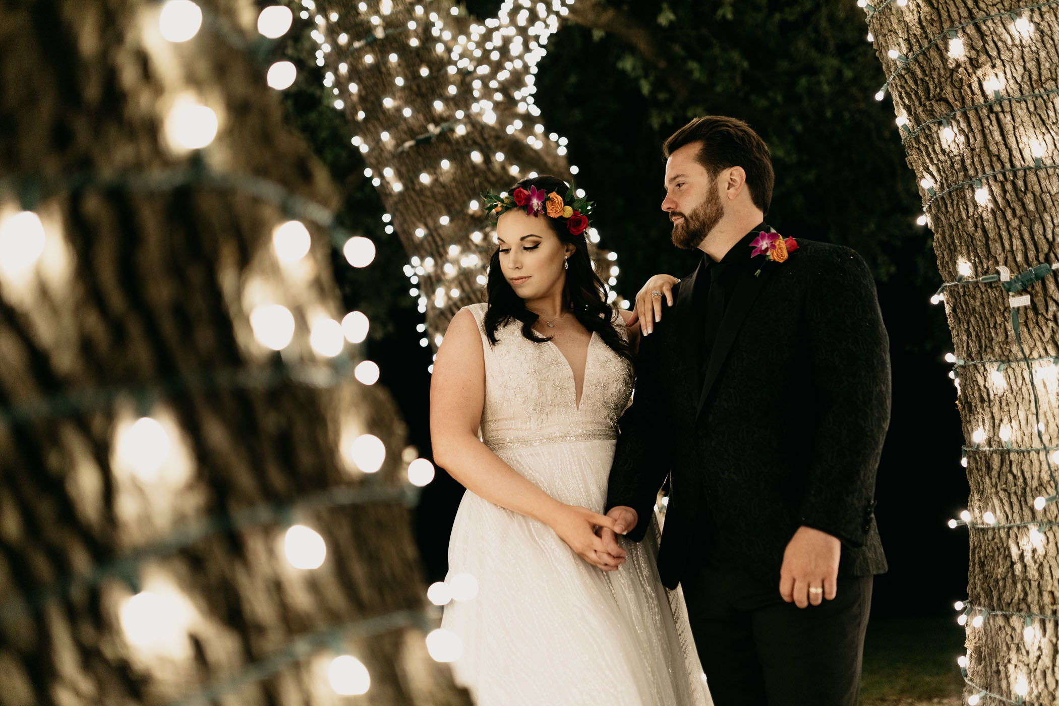 Moody photo of bride and groom standing in a tree of string lights