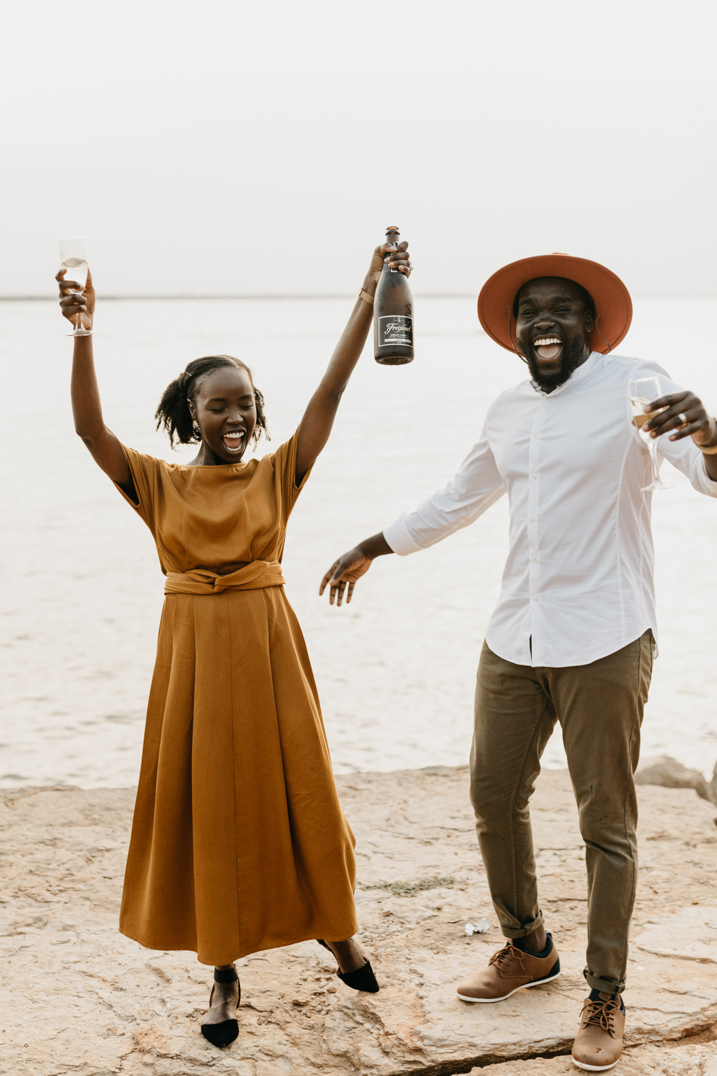 couple being playful with a bottle of champagne during anniversary session in DFW
