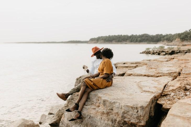 couple cuddling lakeside during anniversary photo shoot