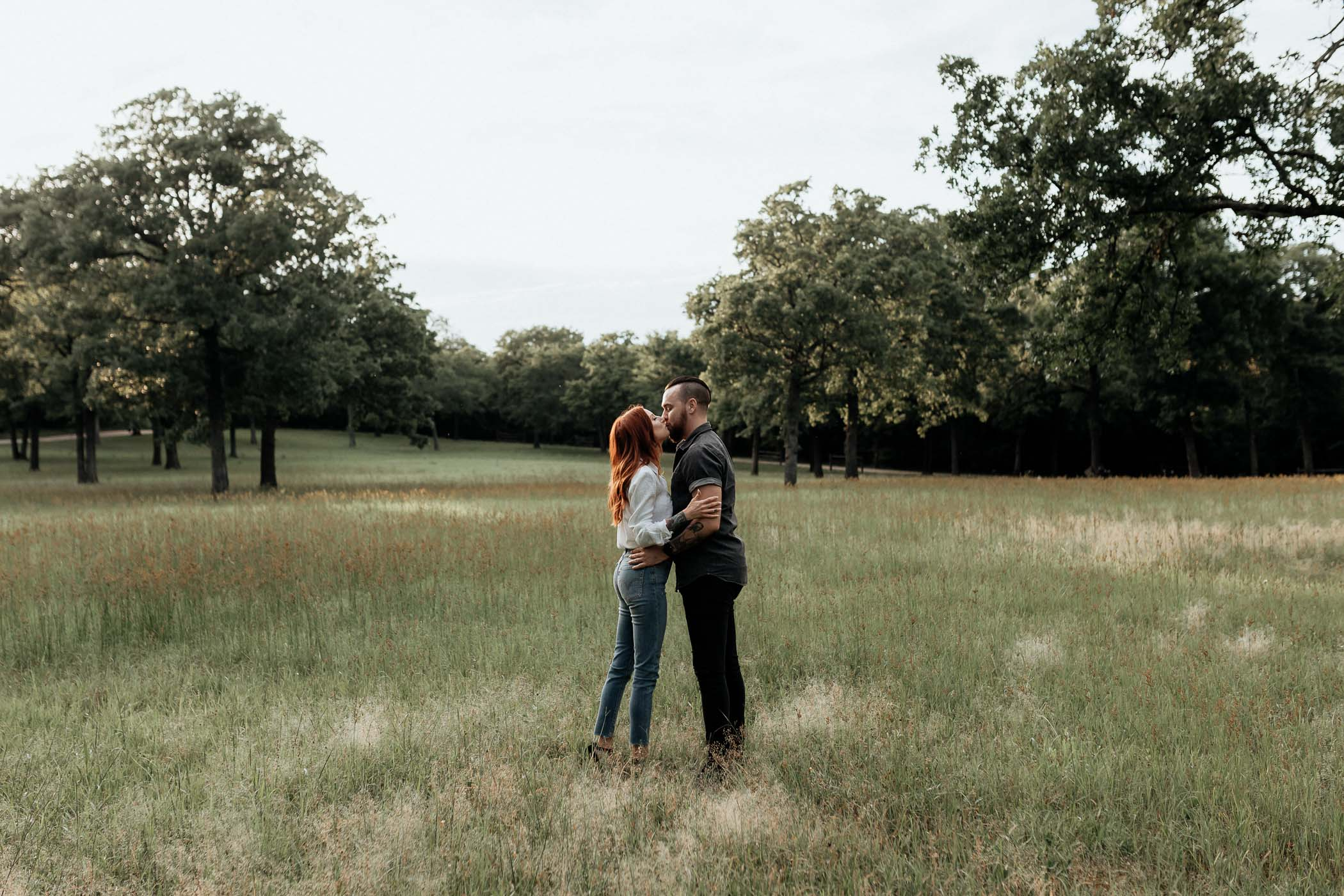 Engaged couple kissing in open field in North Texas