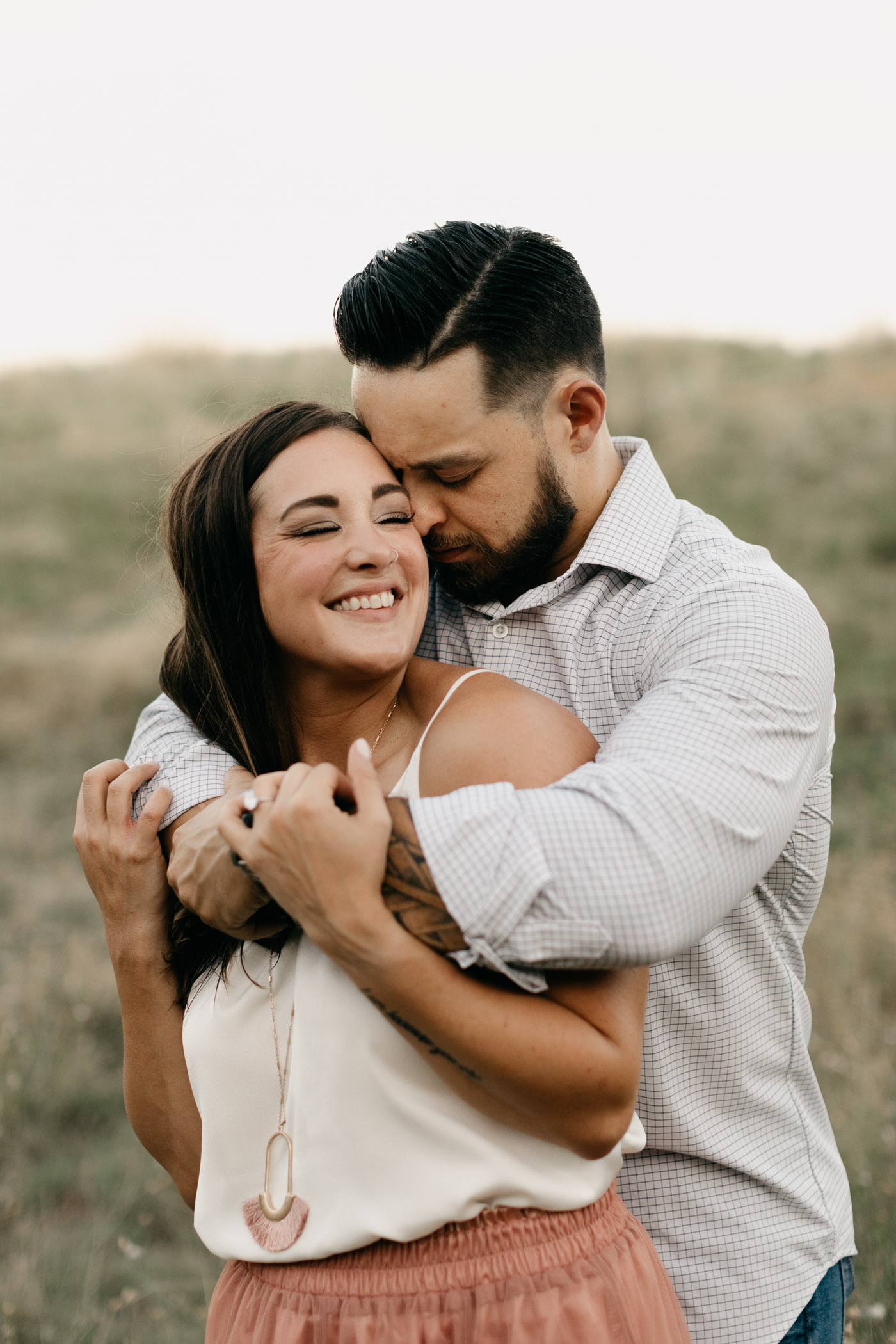 engaged couple snuggling in a field in Texas summer