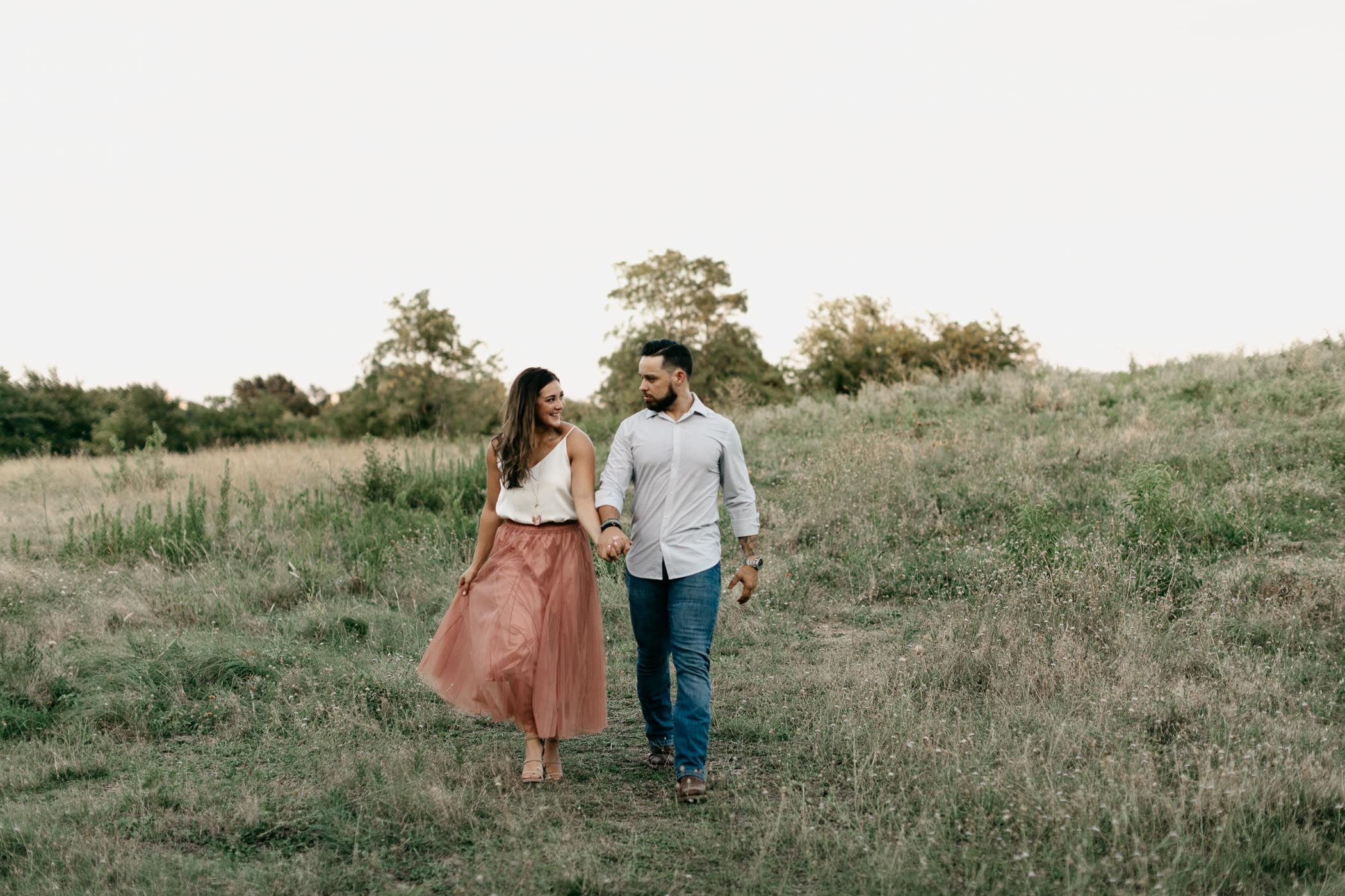 adorable couple walking through field during engagement session in DFW