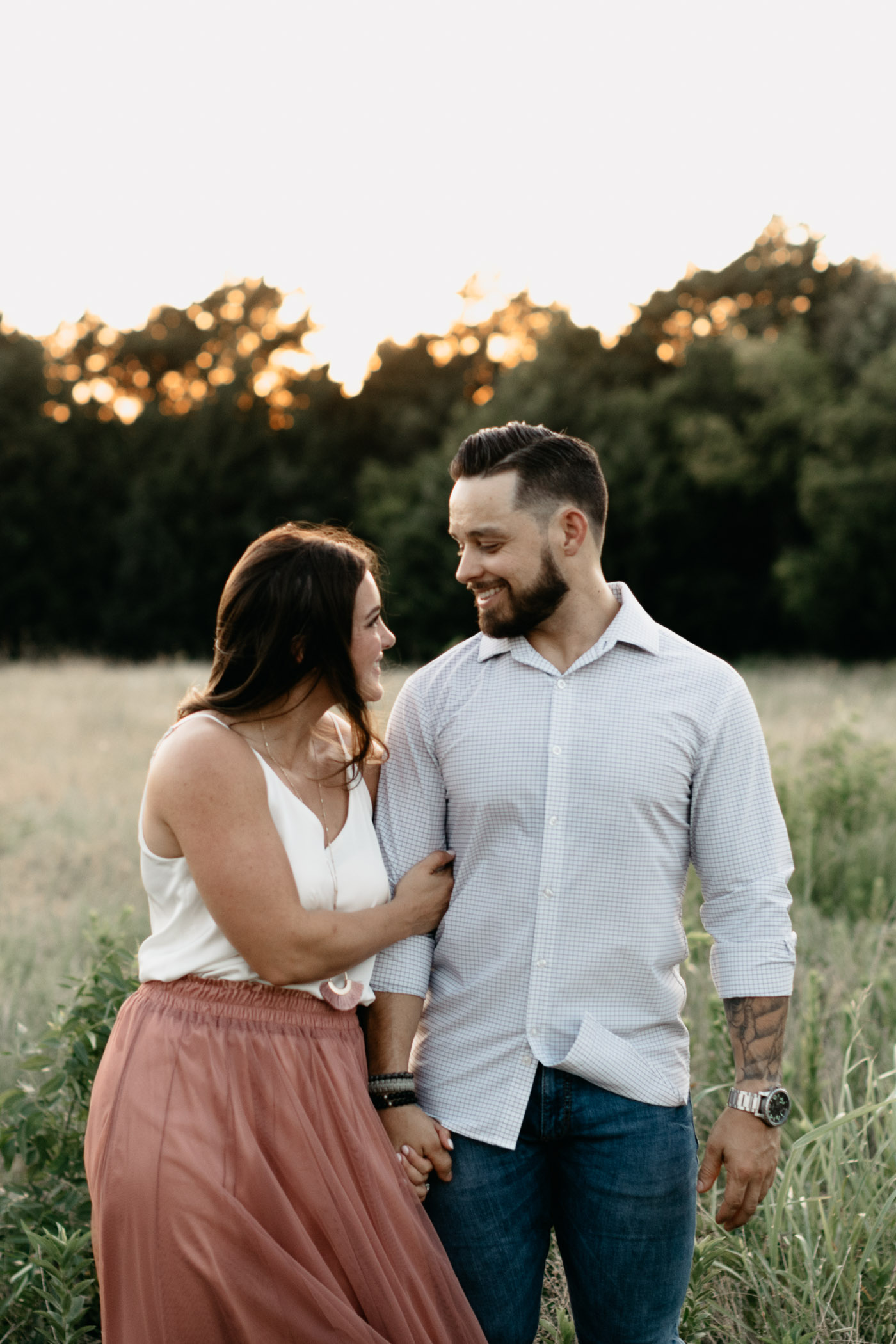 couple looking at each other during engagement session at sunset