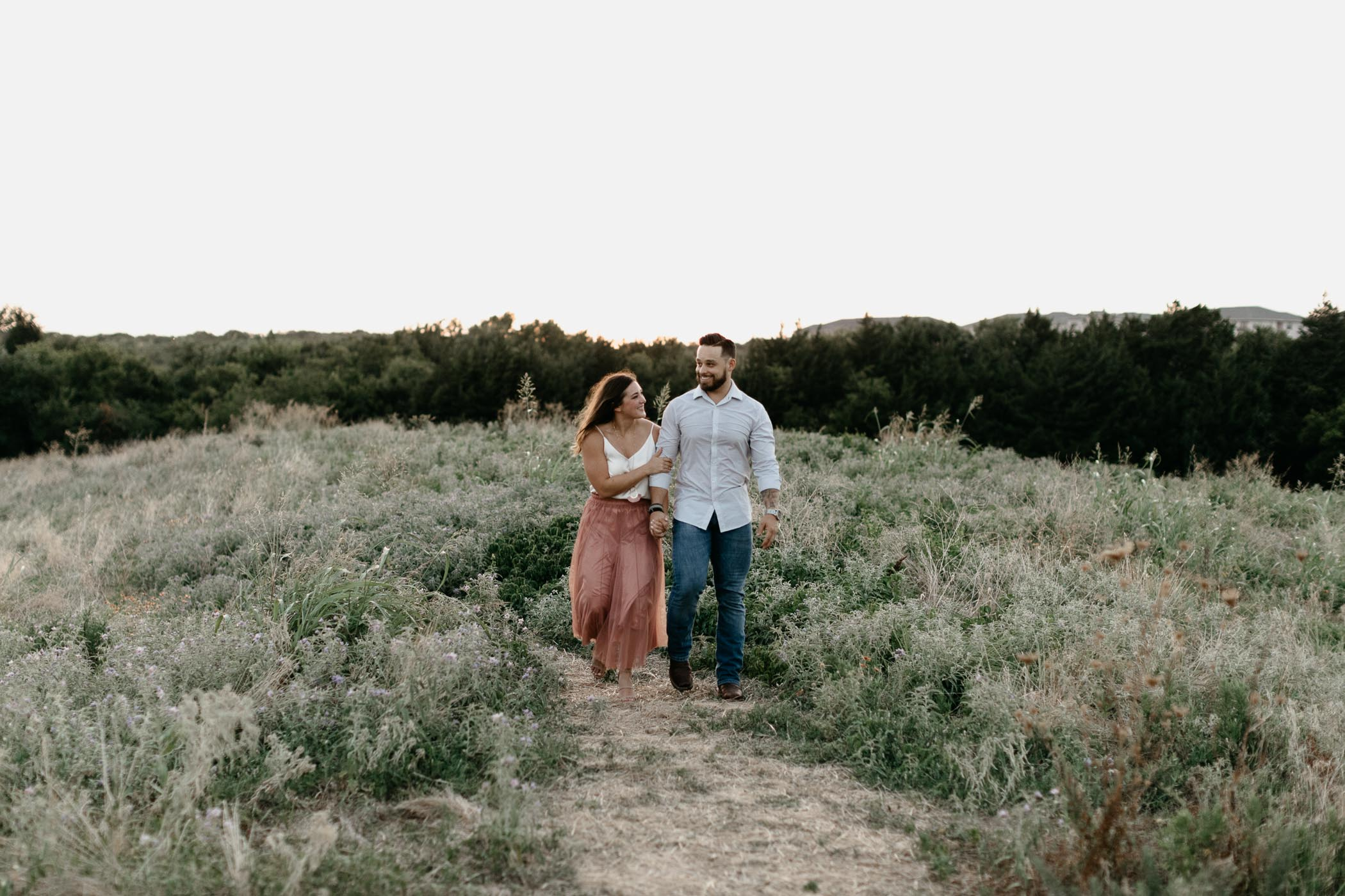 beautiful couple walking on top of a hill in DFW