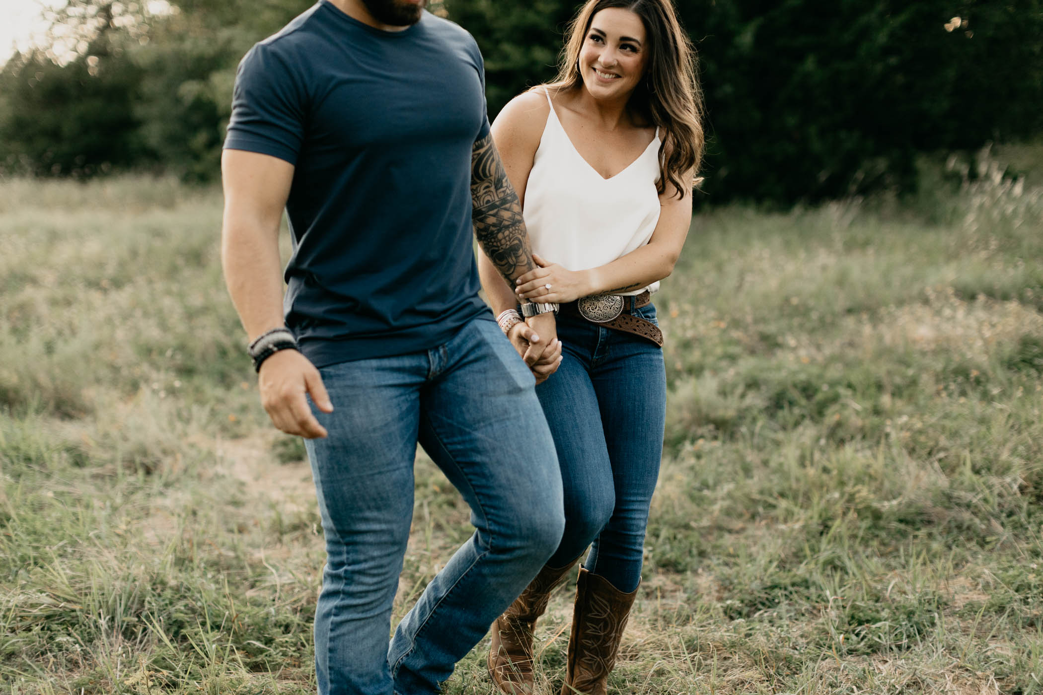 Detail photo of couple walking through field during romantic engagement photos