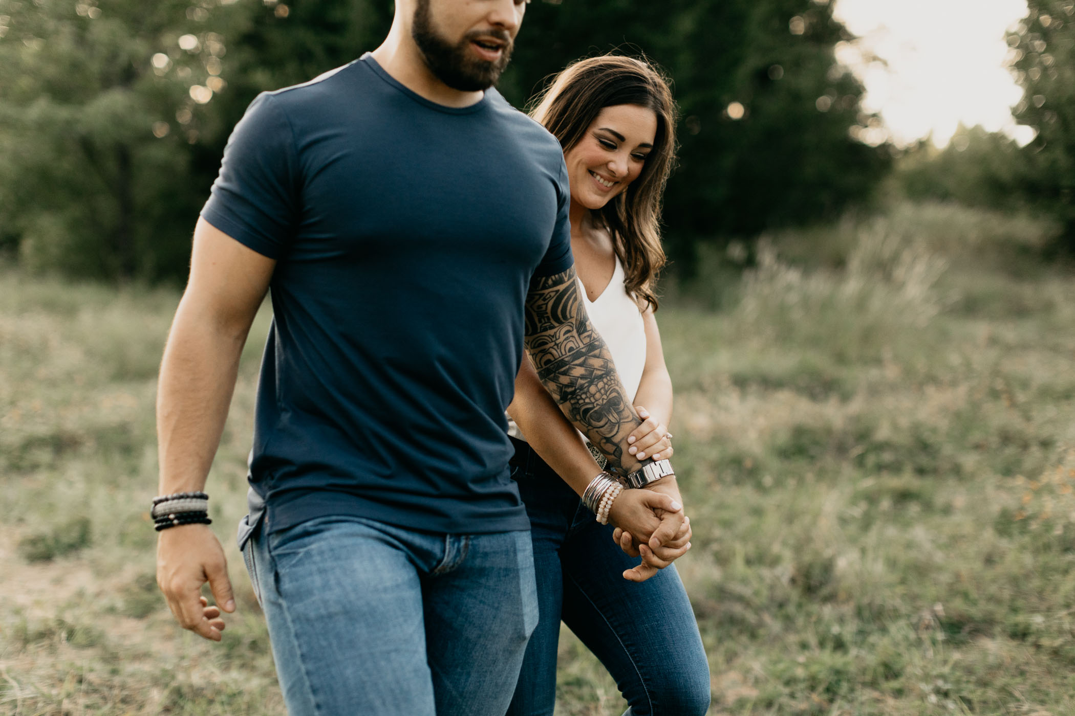 close up photo of couple walking through field during engagement session