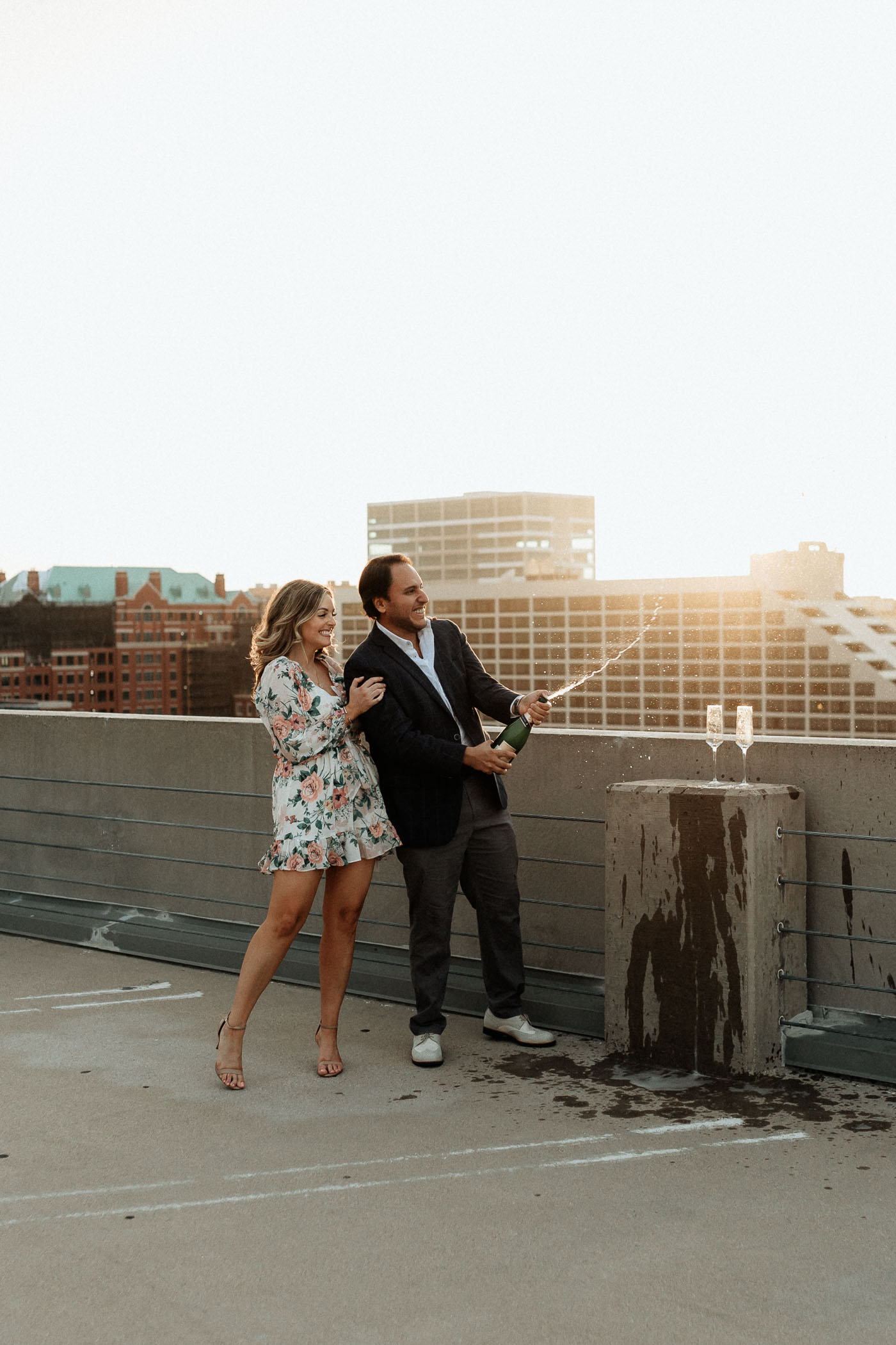 Playful couple popping a bottle of champagne on a rooftop in downtown Fort Worth