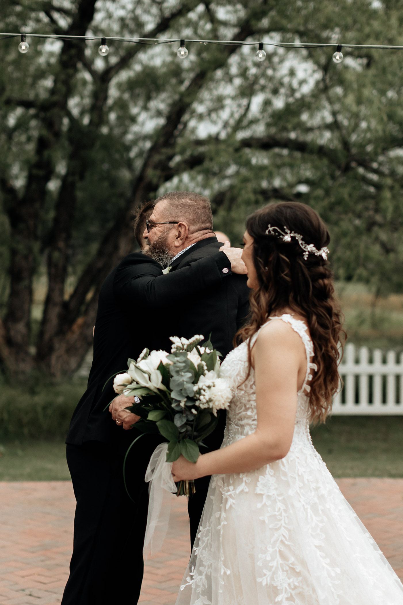 Brides dad hugging groom as he gives his daughter away on her wedding day