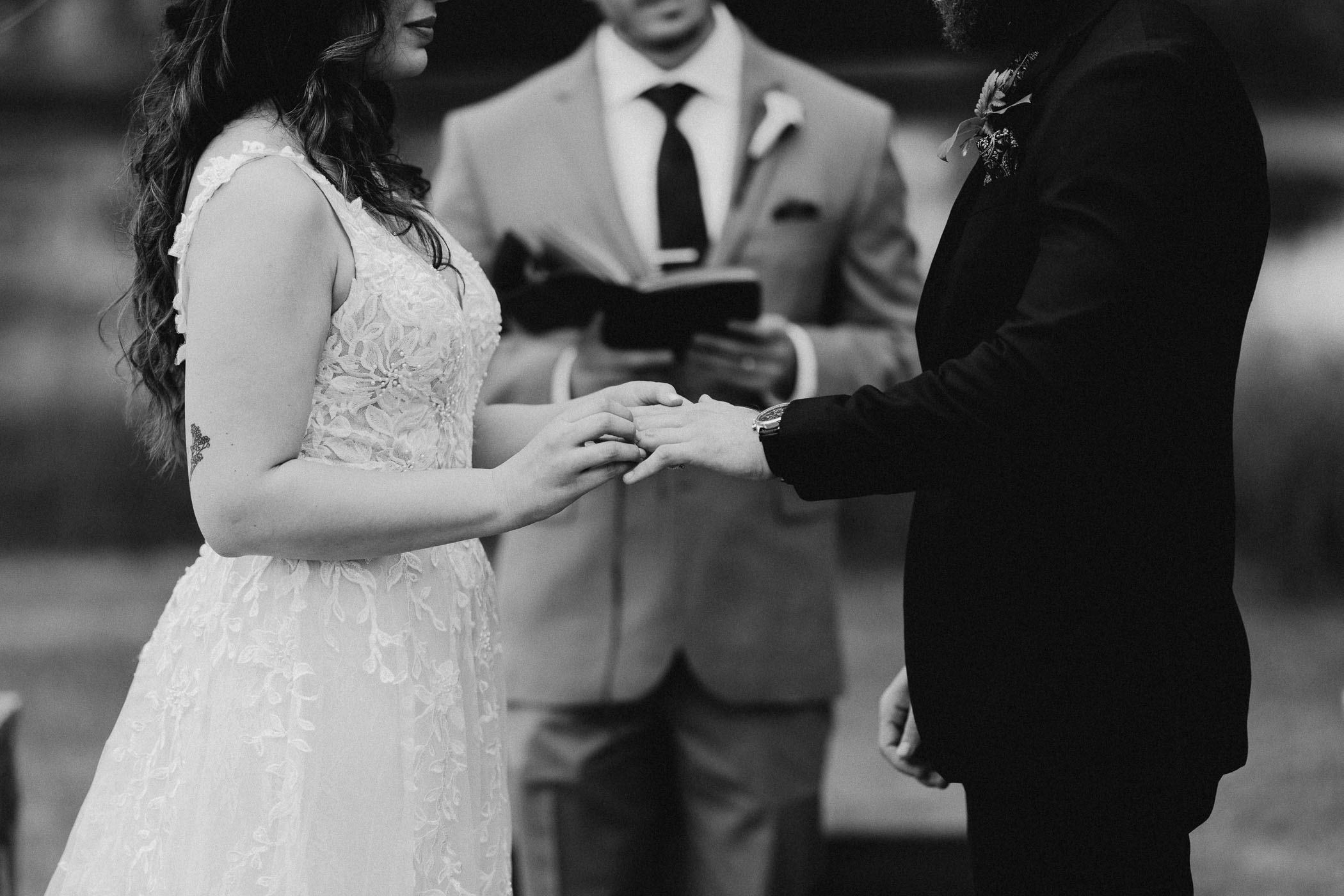 black and white of bride and groom exchanging wedding rings in DFW during pandemic wedding ceremony