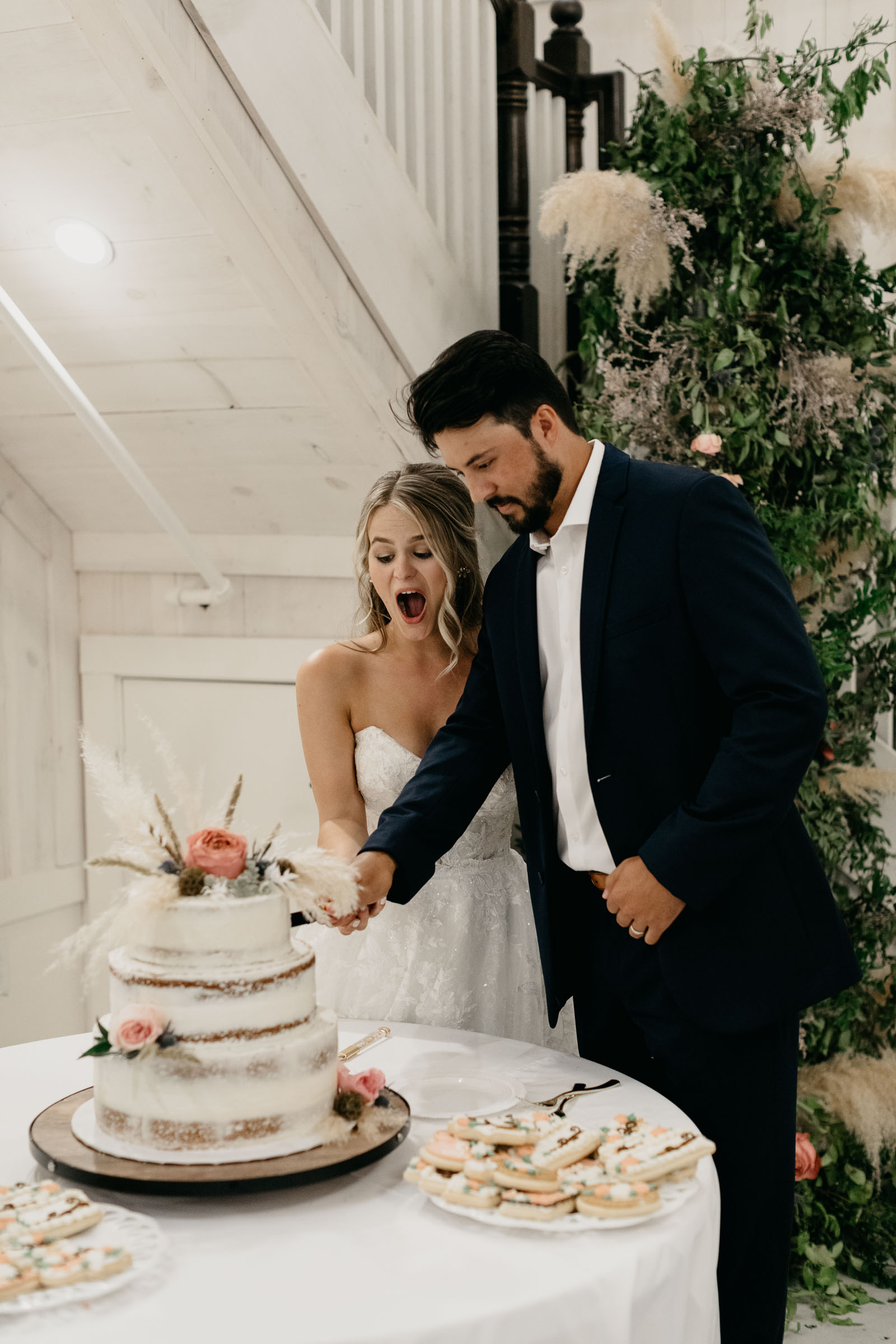 bride and groom laughing and cutting cake in DFW