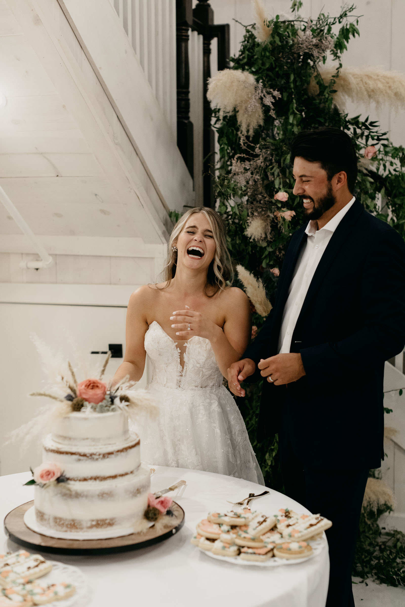 bride and groom laughing as they cut cake in DFW