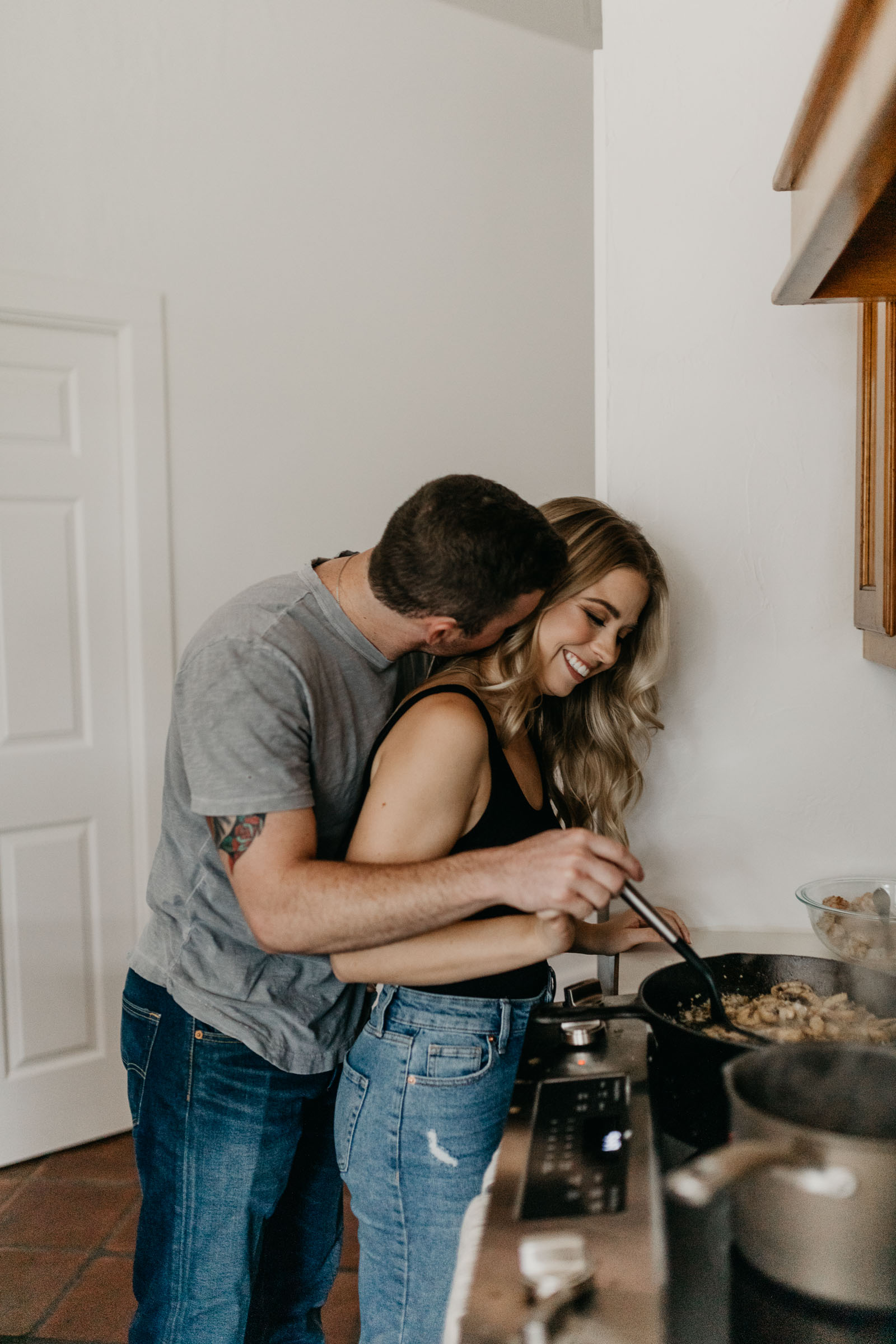 Boy kissing girl on the cheek as she cooks dinner