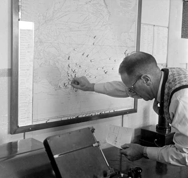 Placing magnets on a map of the South Pacific at Tinkori Hill radio station in 1957.