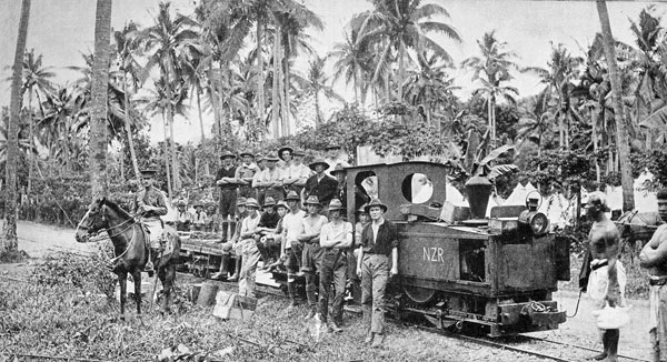 New Zealand's latest railway: Members of the 3rd, Auckland Regiment at Apia, Samoa, and the petrol engine and light railway formerly used by the Germans in carrying material for the construction of the wireless station
