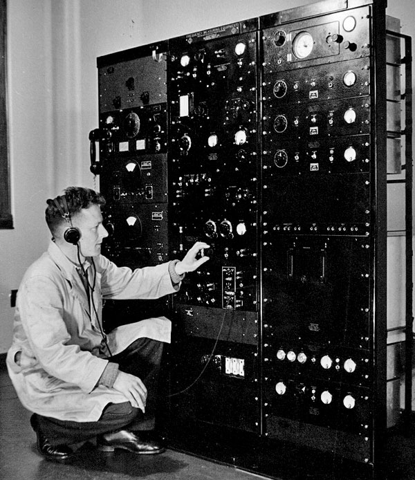 Technican Sid Thompson with the General Radio Primary Frequency Standard equipment.  An HRO receiver is visible near top left.