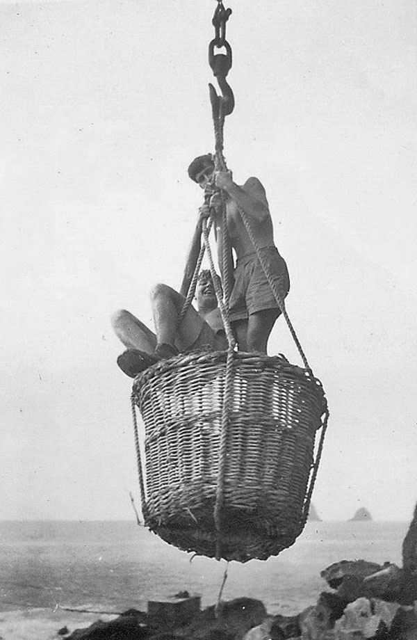 Dressed for a dunking, agriculturalist Bill Porter (left) and radio operator Clyde Williams going ashore at Fishing Rock, Raoul Island, 1950