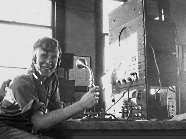 """Meteorologist LAC """"Dick"""" Hay at the small ships desk, Awarua Radio, March 1946"""
