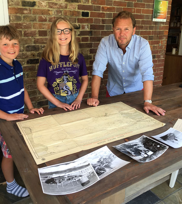 Andrew Brian Agnew (right), son of Captain Brian Agnew, with his children Charlie and Eleanor and some of the family's SS Gothic records, including the lifeboat chart used to navigate Gothic back to New Zealand