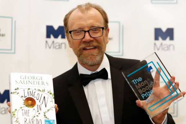 Author George Saunders of the United States with his book 'Lincoln in the Bardo' during a photocall after being announced winner of the 2017 Man Booker Prize, in London, Tuesday, Oct. 17, 2017. (AP Photo/Kirsty Wigglesworth)