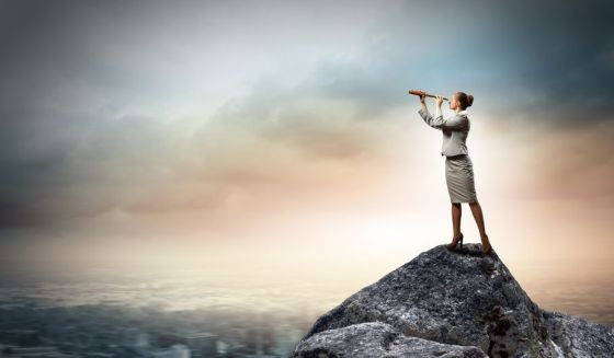 18046450 - image of businesswoman looking in telescope standing atop of rock