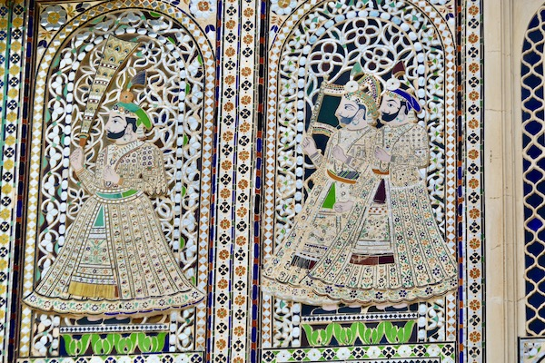 Brightly colored mosaic tile window screens on the upper floors of the City palace in Udaipur