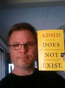 Adult-ADHD-Blog-Creator-Jeff-Emmerson-holding-Dr.-Richard-Sauls-Book-ADHD-Doesnt-Exist