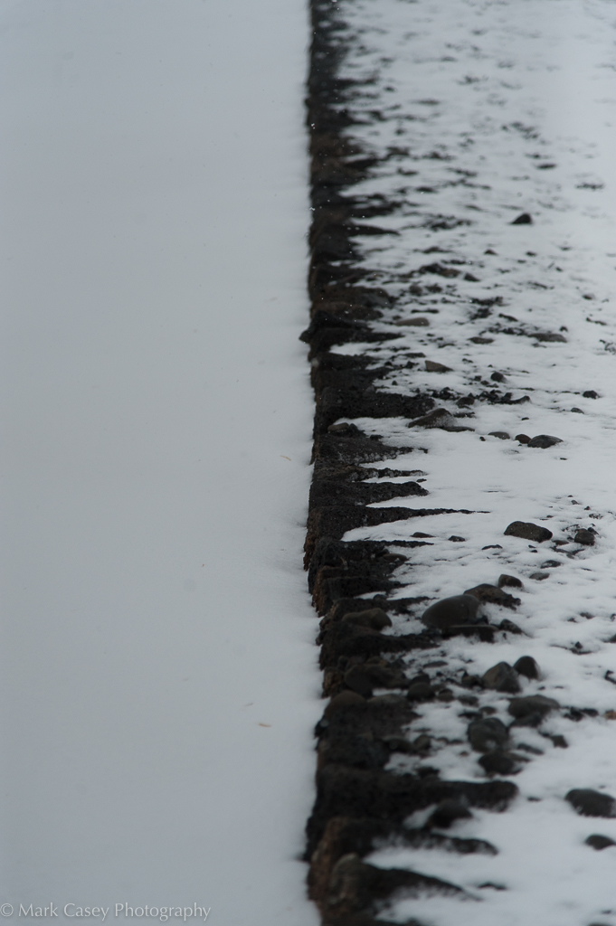 An almost seamless level between a snowdrift and the top of a wall.