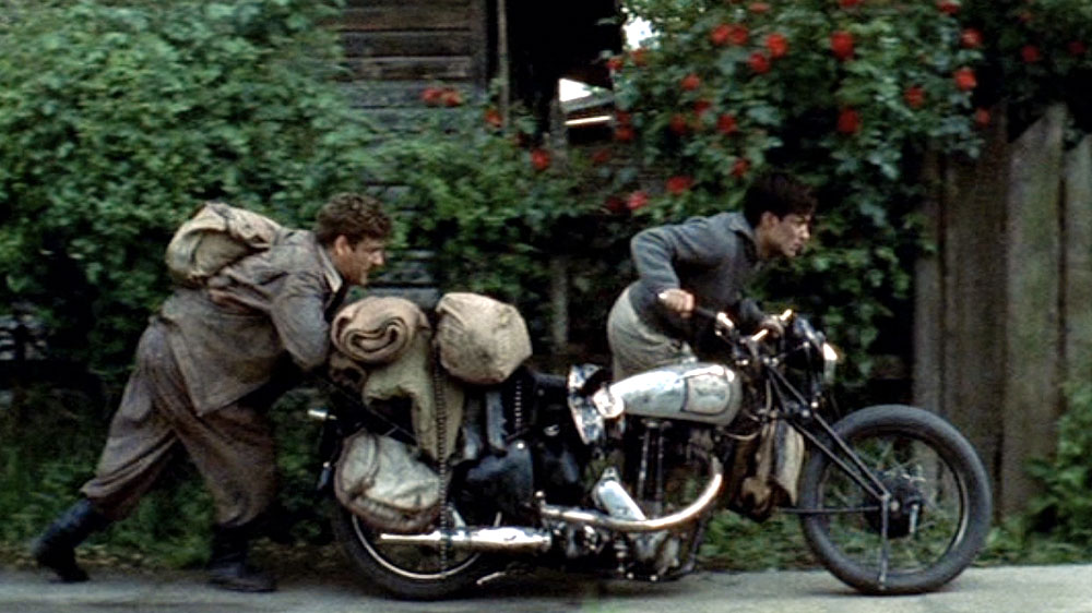 The Motorcycle Diaries (movie, 2004):  Rodrigo de la Serna and Gael García Bernal push a Norton motorcycle