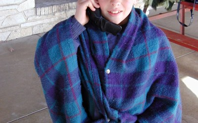 Elliot on the phone in snap blanket
