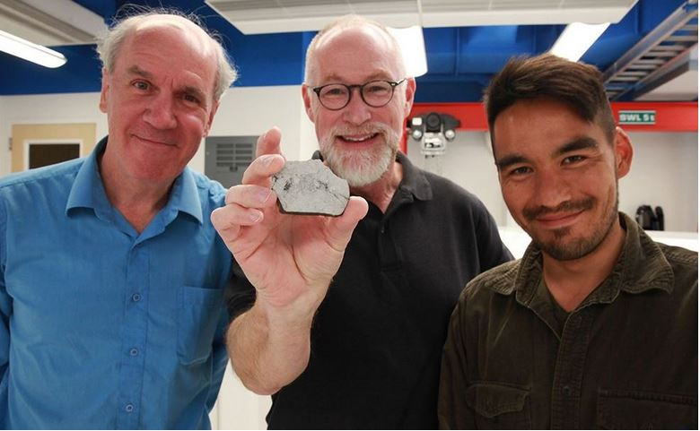 Space scientists holding a sample of Moon rock