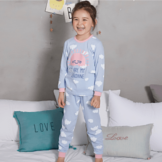 Olomimi My Sunshine Kid Pyjamas Set - a girl with My sunshine pyjamas on standing on a sofa with a nice smile