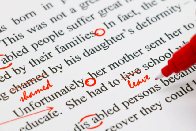 typed writing marked up with a red pen