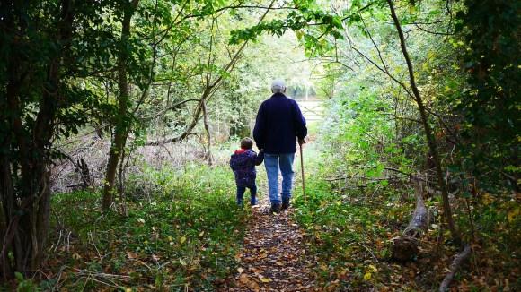 Grandpa and grandkid taking a walk through tthe woods.