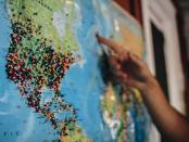 someone pointing to a map of Earth with pins in it