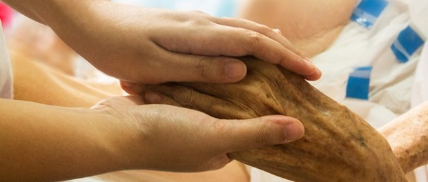 Hospice worker supporting a patient, hand in hand