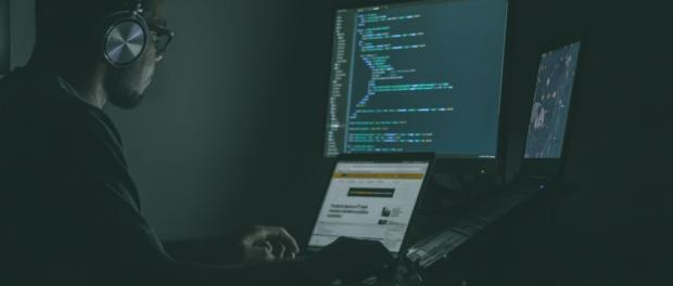 Man with headphones on coding at a computer