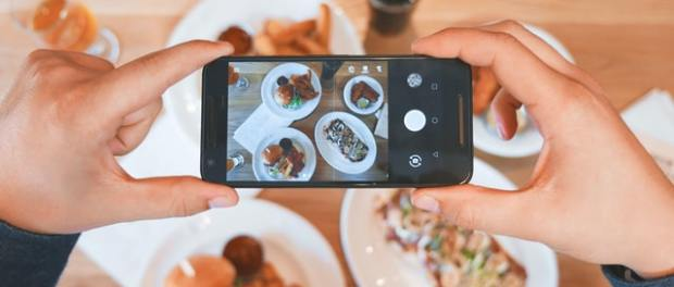 a customer taking photo of meal with smartphone