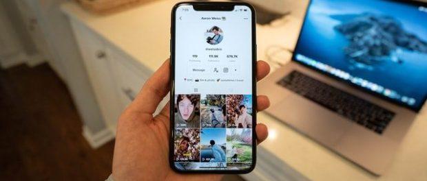 Someone holing a smartphone displaying a TikTok profile.