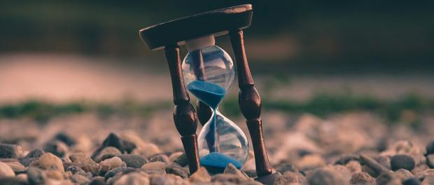 An hour glass on a beach.